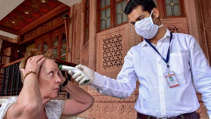 A medic checks the temperature of a tourist as part of precautionary screening in the wake of the coronavirus outbreak, at a hotel in Bikaner Thursday