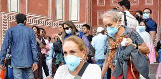 Foreign tourists wear protective masks at the Taj Mahal complex in Agra amid the coronavirus threat   Photo: ANI