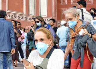 Foreign tourists wear protective masks at the Taj Mahal complex in Agra amid the coronavirus threat | Photo: ANI