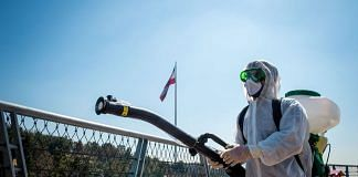 A firefighter wearing protective clothing, mask and goggles, sprays disinfectant on Tabia't bridge pedestrian overpass in Tehran, Iran