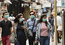 Pedestrians wear protective masks in Khan Market, New Delhi