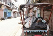 A rickshaw puller wearing a mask dozes off during a COVID-19 lockdown