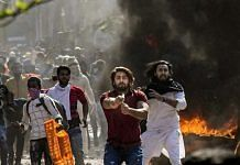 One of the viral images of Shahrukh (in red shirt) pointing his pistol during the Delhi riots in Jaffrabad   Photo: PTI