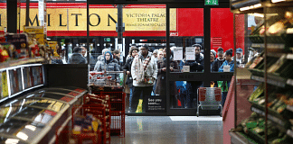 Shoppers wait for a store to open in London