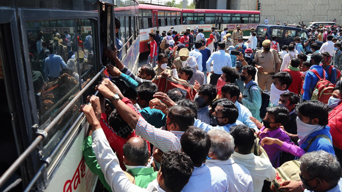 A crowd of migrant workers gather around the UPSRTC buses near the Delhi=Ghaziabad border | Photo : Suraj Singh Bisht | ThePrint