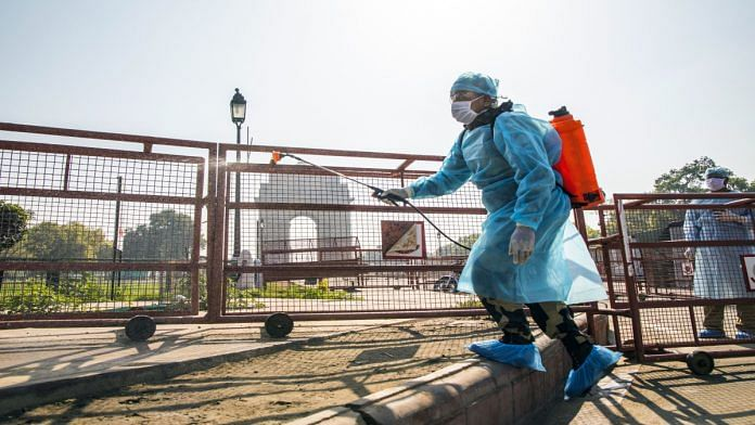 A security personnel spraying disinfectant near India Gate, New Delhi | Prashanth Vishwanathan | Bloomberg
