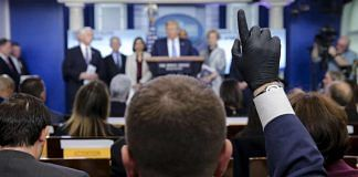 A member of the media wears protective gloves during a briefing by US president Donald Trump on the administration's response to coronavirus, on 16 March 2020 | Oliver Contreras | Sipa via Bloomberg