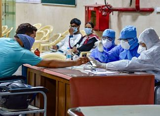 Medics interact with a patient at a help desk, set- up in view of coronavirus pandemic, at Gandhi Hospital in Hyderabad on 14 March