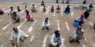 Men sit on the ground with lines drawn with chalk to maintain social distancing during a partial Covid-19 lockdown in Pakistan. Photo | ANI