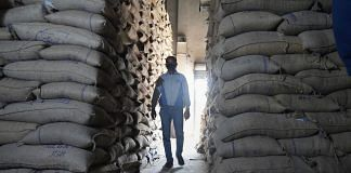 File photo | An employee inspects a godown of Food Corporation of India (FCI) where rice bags are being stored during a nationwide lockdown, in Srinagar | PTI