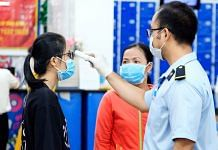 Customers have their temperature checked at the entrace to a Co.opmart supermarket during a partial lockdown imposed due to the coronavirus in Ho Chi Minh City, Vietnam. | Photographer: Maika Elan | Bloomberg