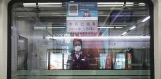 A platform attendant stands on duty at a metro station in Wuhan | Bloomberg