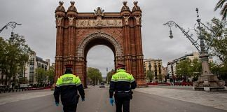 Citizen security officers of the Mossos d'Esquadra police force walk to the Arc de Triomf monument in Barcelona on April 1. | Bloomberg