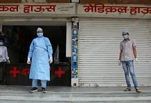 Men in protective gear stand outside a medical store in Bhilwara, Rajasthan, on 27 March | Photo: Manisha Mondal | ThePrint
