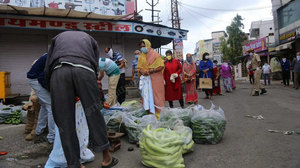 Residents of Bhilwara queue up to buy vegetables as a policeman (right) ensures social distancing on 27 March | Photo: Manisha Mondal | ThePrint