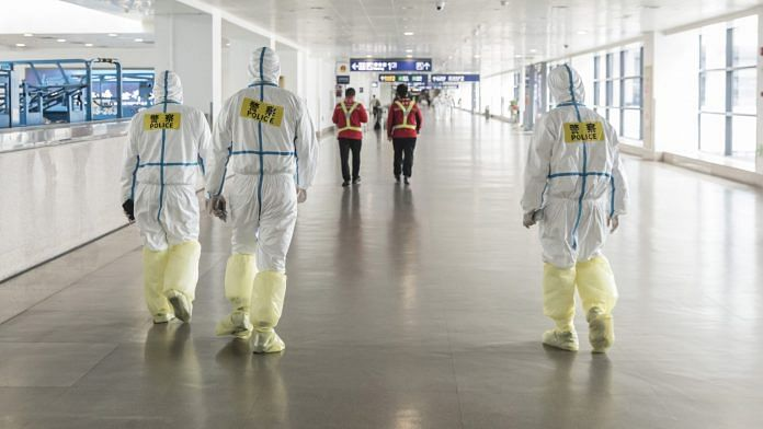 Representational image. Airport employees wear full body protective suits at Pudong International Airport in Shanghai on 28 March. | Photographer: Qilai Shen | Bloomberg
