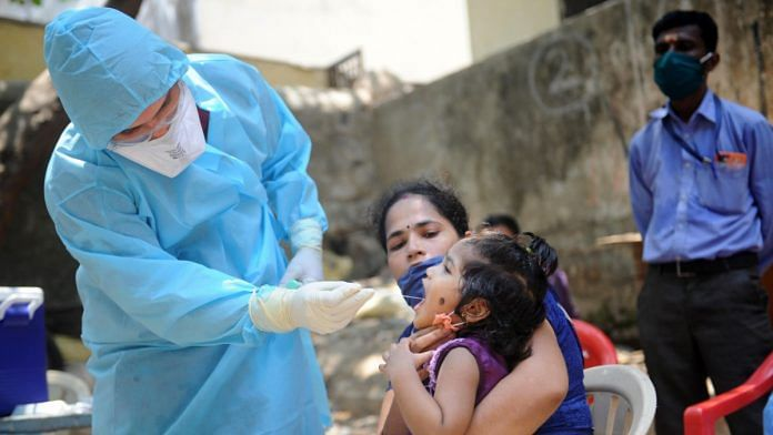 A doctor takes a swab from a child to test for Covid-19 at Kalyanwadi in Dharavi slums, Mumbai on 16 April | PTI