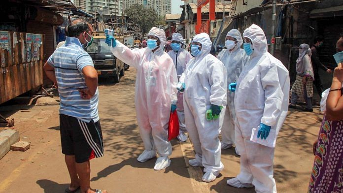 Doctors wearing protective suits check residents with an electronic thermometer inside a slum in Worli, Mumbai | PTI