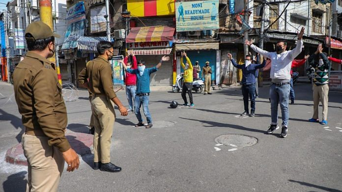 Policemen hold up people flouting the lockdown at City Chowk in Jammu, on 30 March 2020 | PTI