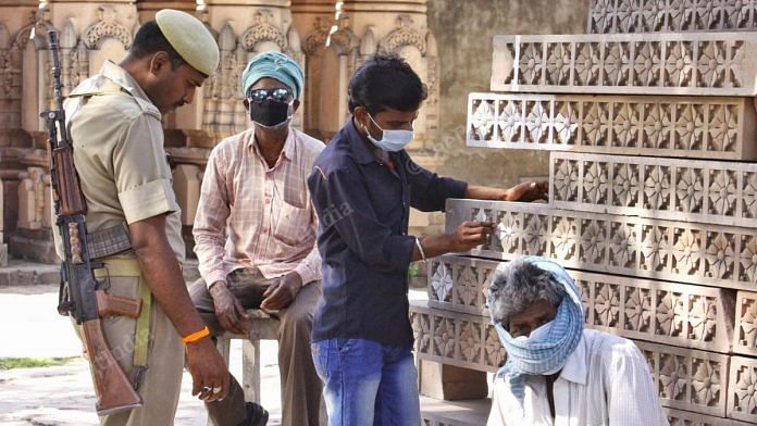 Labourers and a policeman at the Ram Mandir karyashala in Ayodhya Thursday | Photo: Praveen Jain | ThePrint