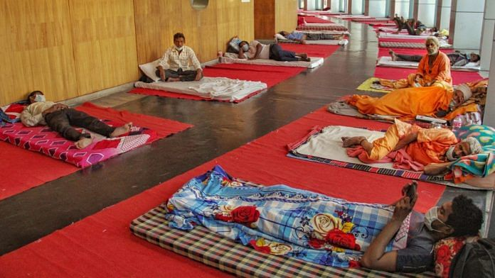 Migrant workers rest inside the Yamuna Sports Complex, which has been converted into a makeshift shelter during the ongoing COVID-19 lockdown, in New Delhi, on 5 April 2020 | PTI