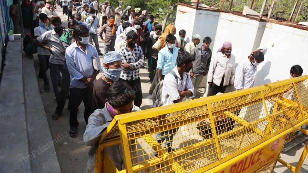 Homeless people and migrant workers stand in queue for food at a shelter home in Delhi | Manisha Mondal| ThePrint