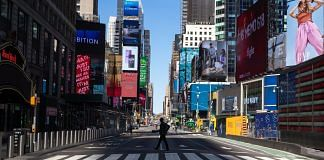 A pedestrian crosses a nearly empty street in the Times Square neighborhood of New York, US | Bloomberg