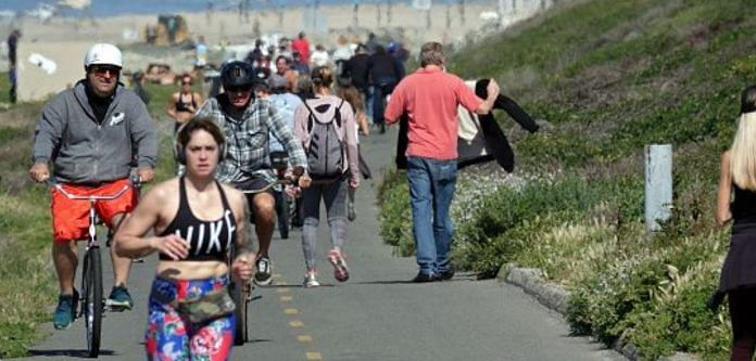People exercise along a bike path on March 28, 2020 in Huntington Beach, California. Photo | Bloomberg