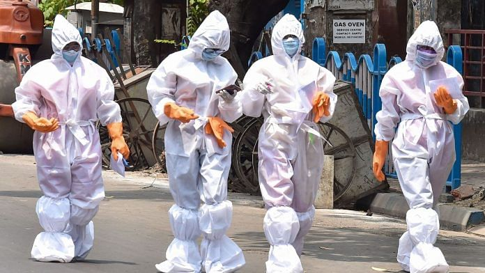 Health workers wearing protective suits walk on a street in Kolkata | Representational image | PTI