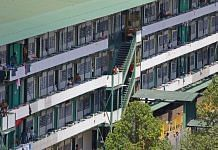 Migrants workers outside their dormitory rooms at Cochrane Lodge II in Singapore on 16 April | Bloomberg