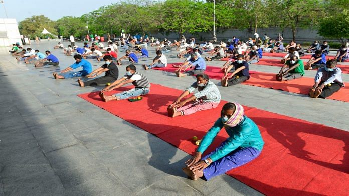 People residing in the makeshift camp at Yamuna sports complex in Delhi perform yoga earlier this week