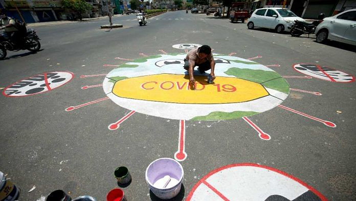 A man draws a Covid-19 awareness message on a road in Ahmedabad | Representational image | ANI