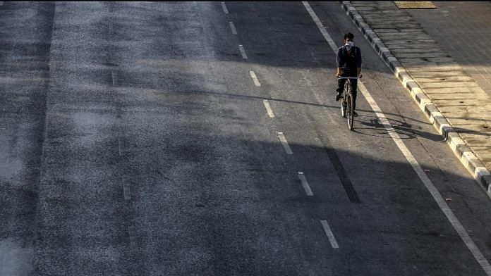 A cyclist travels on an empty street in the Marine Drive area during a lockdown imposed due to the coronavirus in Mumbai, India. | Photographer: Dhiraj Singh| Bloomberg