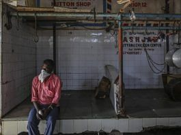 A person wears a bandana as a mask while seated in a meat shop during a lockdown imposed due to the coronavirus in Mumbai. | Photographer: Dhiraj Singh| Bloomberg