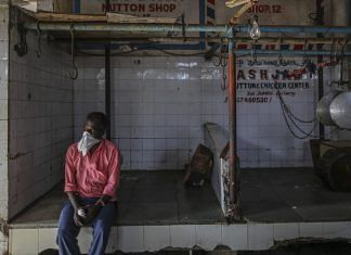A person wears a bandana as a mask while seated in a meat shop during a lockdown imposed due to the coronavirus in Mumbai.   Photographer: Dhiraj Singh  Bloomberg