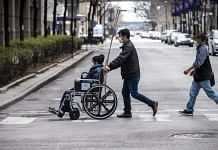 A man pushes a wheelchair towards Northwestern Memorial Hospital in Chicago, Illinois, U.S. | Photographer: Christopher Dilts | Bloomberg