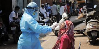 A medic collects swab from the mouth of a woman resident for COVID-19 test in a containment zone at Kurla, Mumbai, Tuesday, April 14, 2020. | PTI