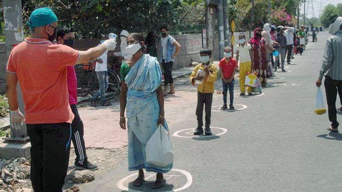 A health worker checks the temperature of a woman, during distribution of food among the needy, amid the nationwide lockdown to curb the spread of coronavirus, at Sec-33 in Noida. | PTI