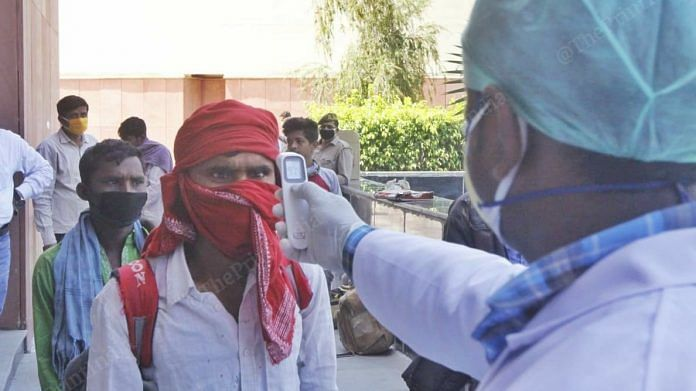 A doctor checks the temperature of a migrant worker as part of the screening process. (representational image) | Photo: Praveen Jain | ThePrint