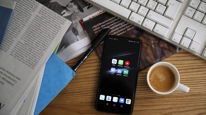 A smartphone sits next to a cup of espresso on the desk of a home office in an arranged photograph taken in Bern, Switzerland. (Representational Image) | Photographer: Stefan Wermuth | Bloomberg