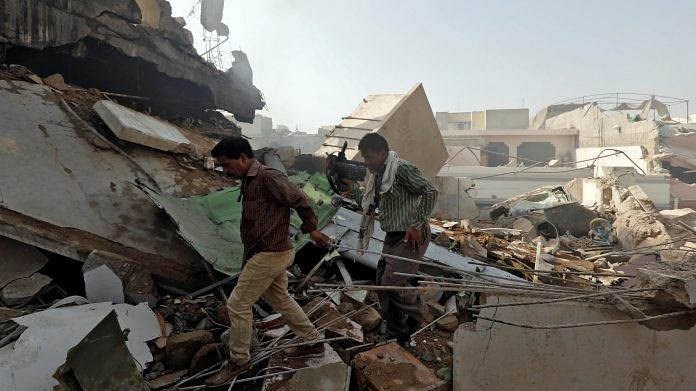 Men walk on the debris at the site of a passenger plane crash in a residential area near an airport in Karachi, Pakistan on Friday.   ANI