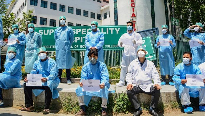 Srinagar: Senior doctors at Super Speciality Hospital, Srinagar display placards during a protest against alleged manhandling of two senior doctors by the police while they were duty, during ongoing COVID-19 lockdown, in Srinagar, Tuesday, May 26, 2020. (PTI Photo)