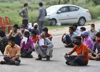 Migrant labourers have been on a quest to get back home. Here, they are seen sitting on the road near the Uttar Pradesh-Bihar border as they wait for their turn to be screened | Suraj Singh Bisht | ThePrint
