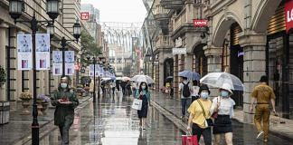(Representational Image) walk with umbrellas past stores in Wuhan on 30 April | Photo: Qilai Shen | Bloomberg
