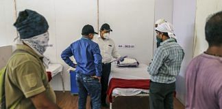 Officials and workers check a plan as the finishing touches are applied to a ward at a dedicated Covid Heath Centre at the Bandra Kurla Complex exhibition ground in Mumbai, India | Bloomberg