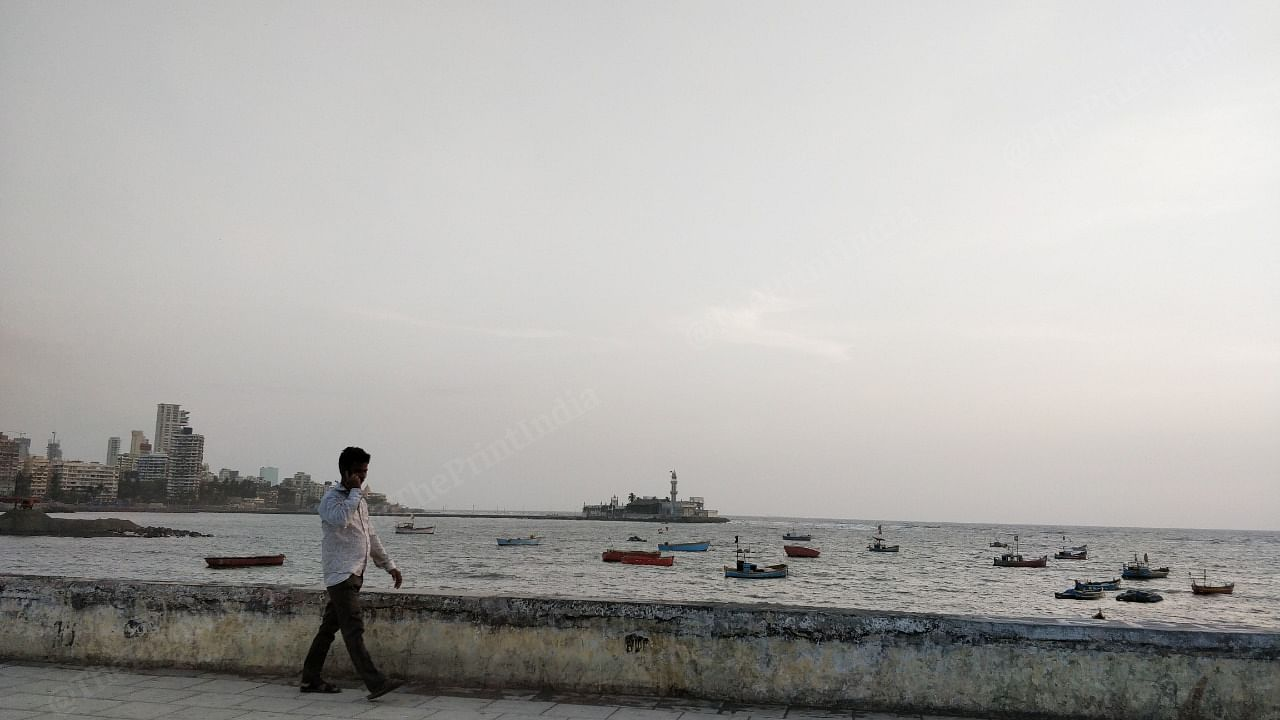 A man walks by on the Cumbaala Hill with the Mumbai skyline and the Haji Ali mosque in the background   Photo: Swagata Yadavar   ThePrint
