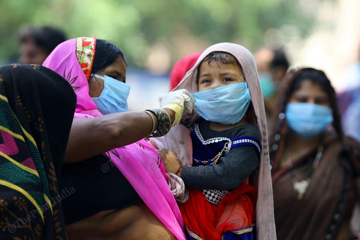 A mother protecting her child by covering her mouth from the mask and save her from coronavirus at the New Delhi railway station| Photo | Suraj Singh Bisht | ThePrint