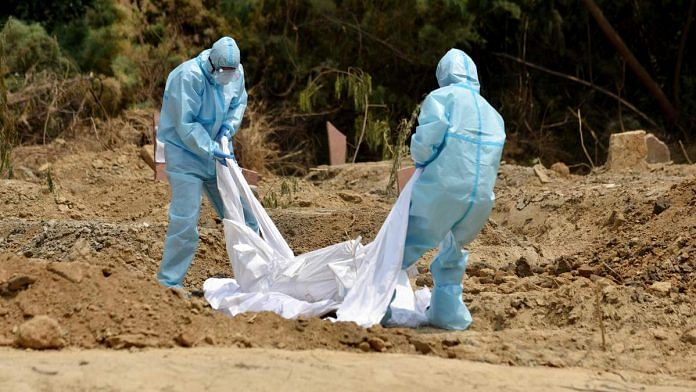 Health workers in protective gear bury the body of a Covid-19 victim in Delhi | Photo: ANI
