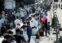 Migrant labourers in line to board a bus in Mumbai's Dharavi to railway station Tuesday | PTI