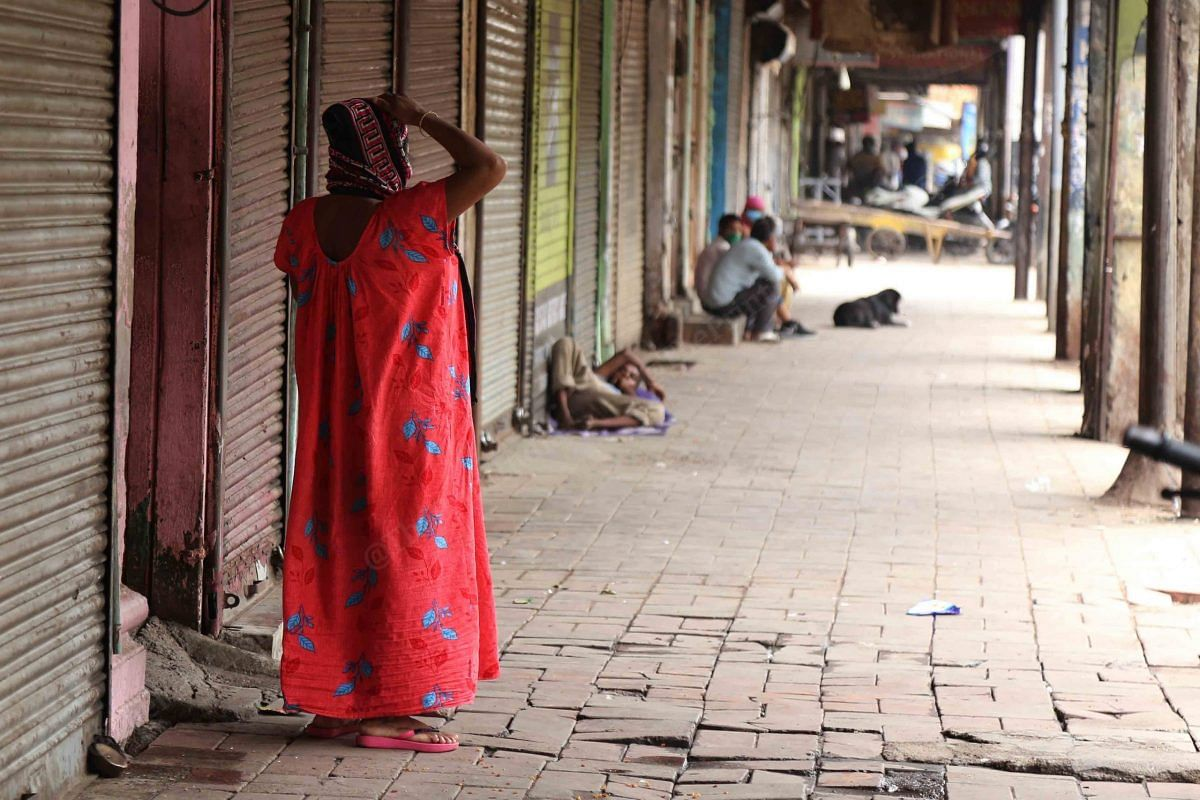 A woman stands outide her home in the empty alley   Photo: Manisha Mondal   ThePrint